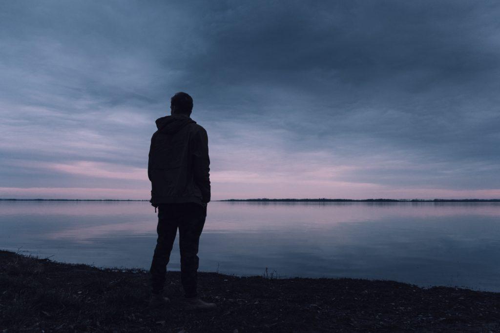 mężczyzna nad brzegiem jeziora