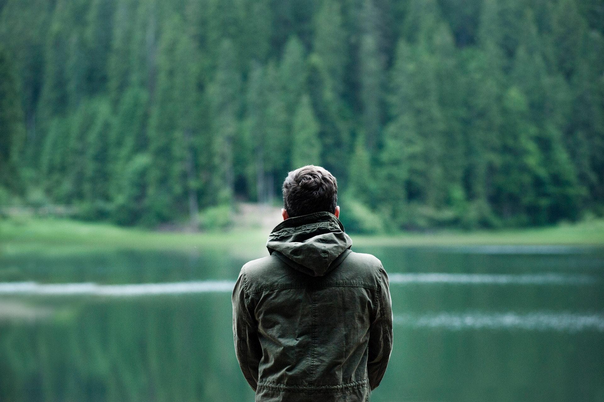 mężczyzna patrzy na jezioro i las