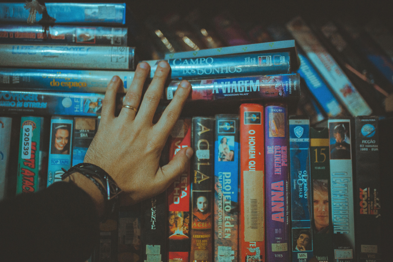 ręka dotykająca półki z filmami