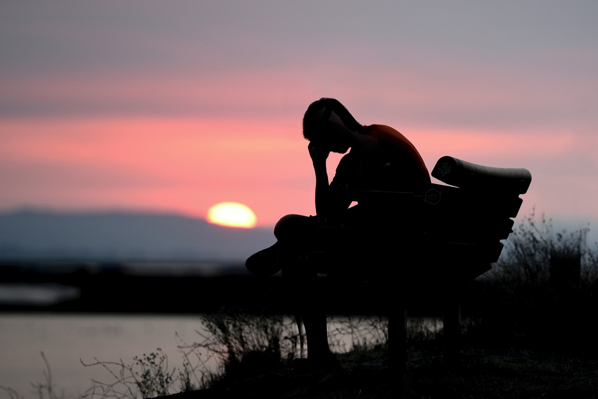zastanawiający się nad czymś człowiek przy zachodzie słońca