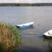 dwie łódki zacumowane przy brzegu jeziora