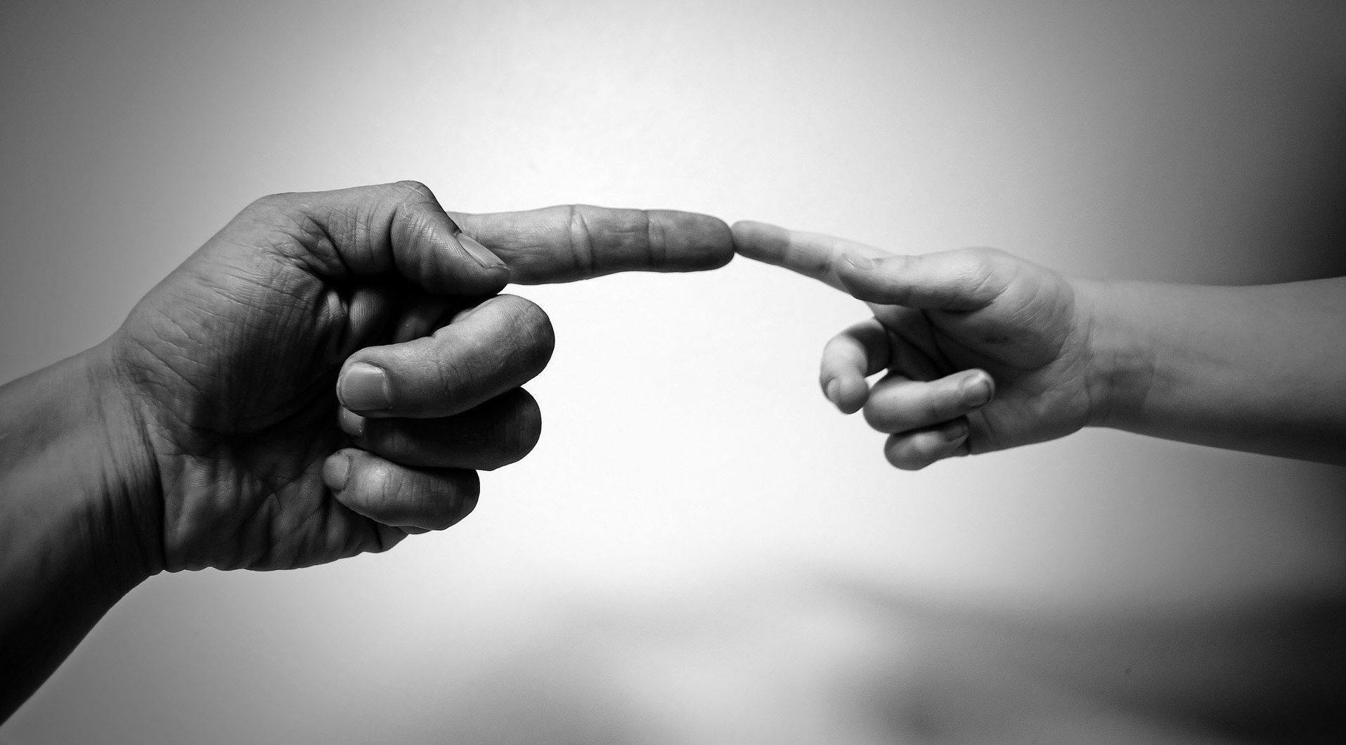dwie dłonie stykające się palcem wskazującym