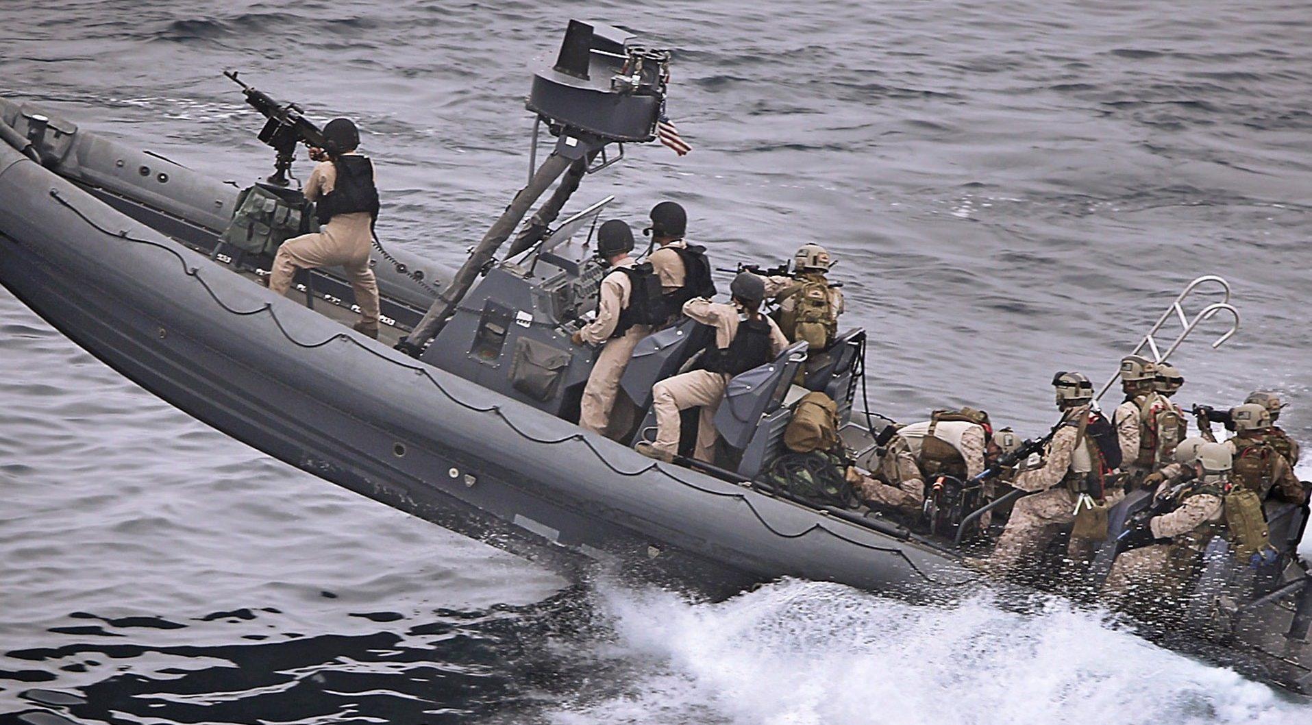 żołnierze płynący na łodzi bojowej