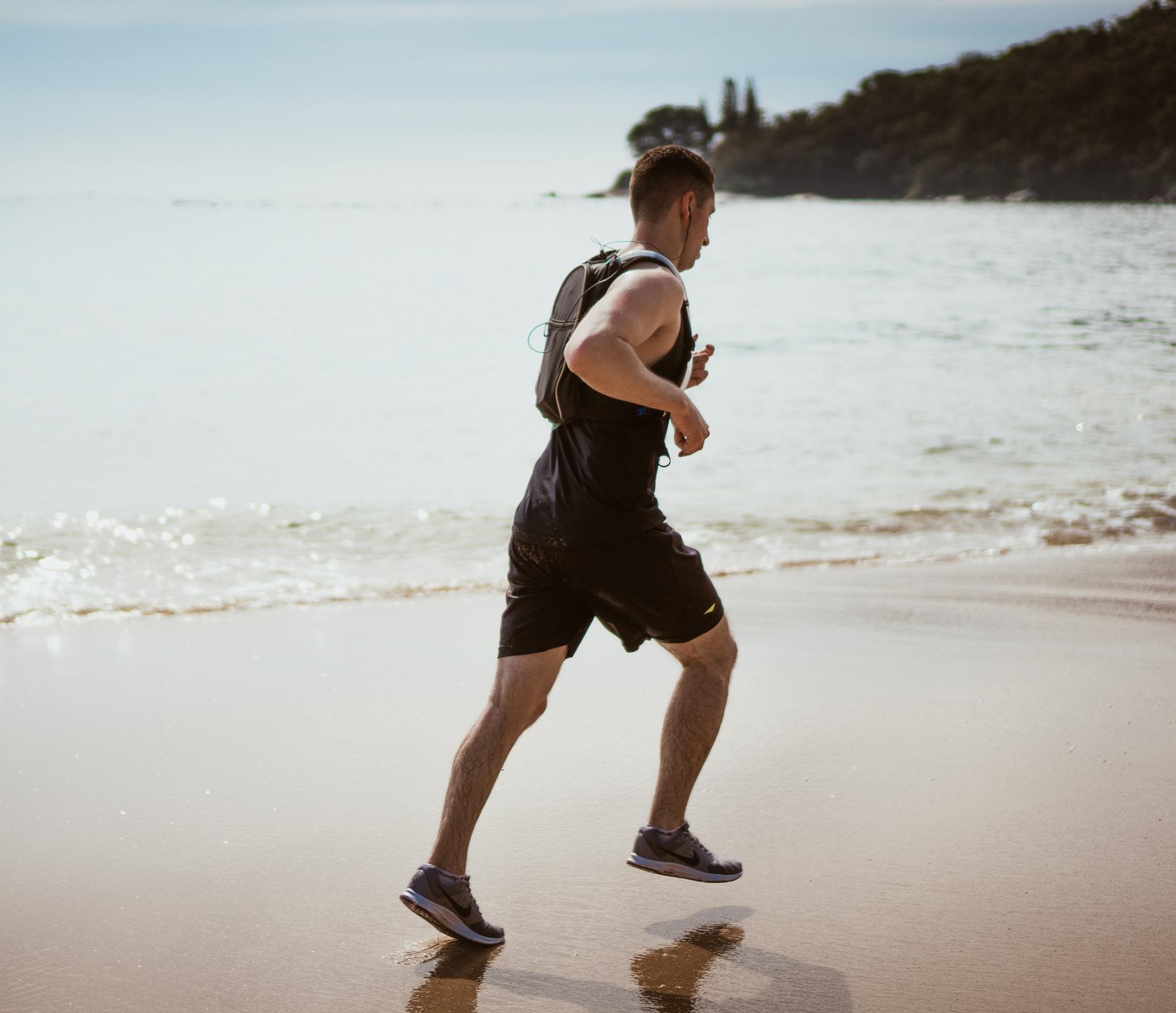 mężczyzna biegnący przez plażę