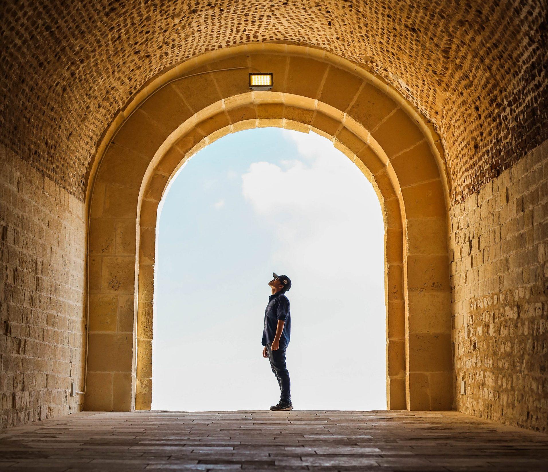 mężczyzna stojący w bramie, spoglądający w górę