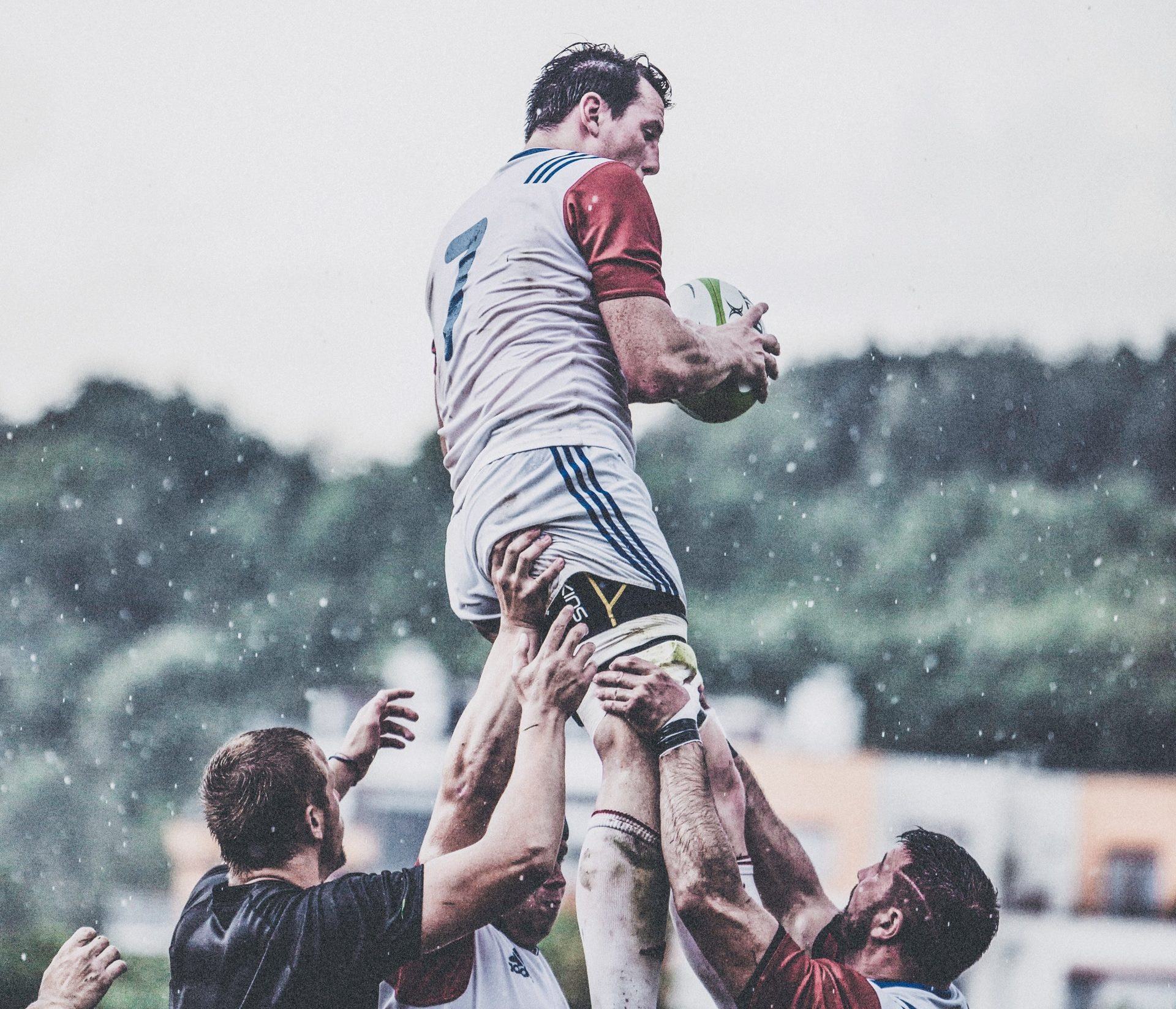 kilku zawodników rugby podnoszących jednego z graczy do góry