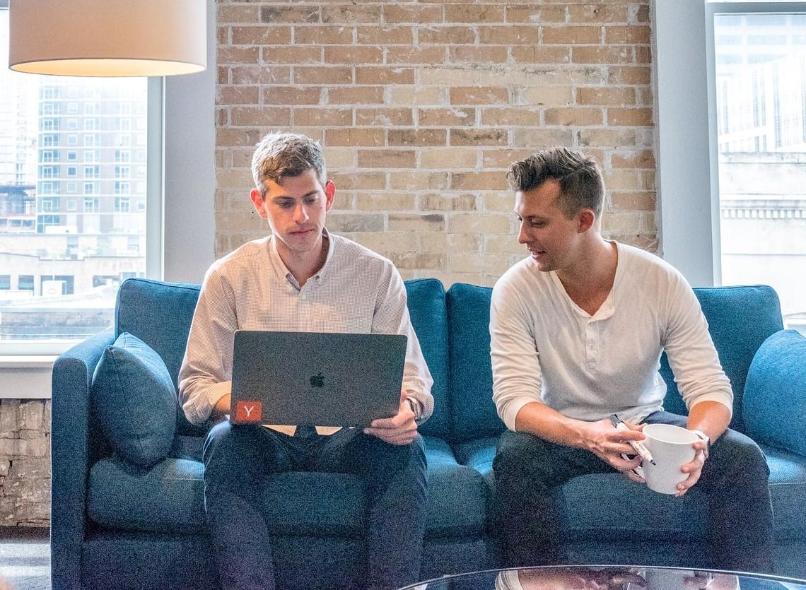 dwóch mężczyzn dyskutujących przy laptopie