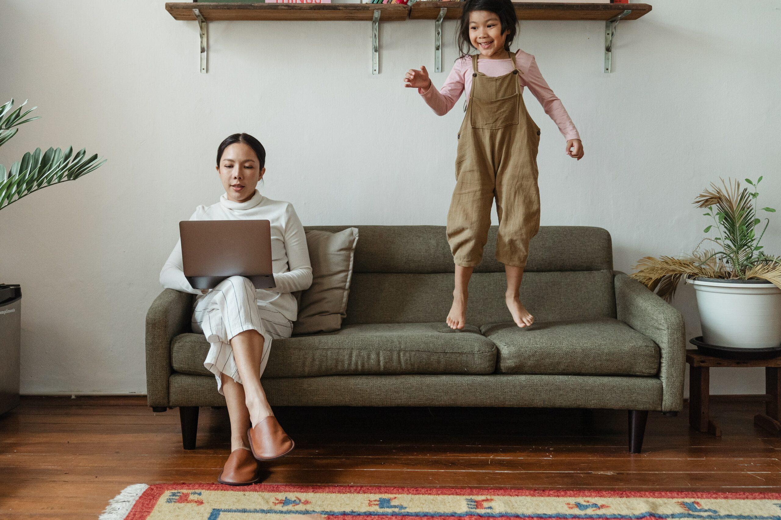 kobieta pracująca na laptopie z dzieckiem, które jej przeszkadza